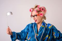 Screaming crazy housewife in a dressing gown and curlers with a ladle in her hand stock images