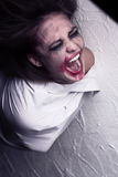 Screaming crazy woman. With smeared makeup in straitjacket Stock Photos