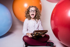 Screaming curly teen girl in glasses with wooden abacus on the b Royalty Free Stock Image