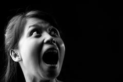 Screaming in dark. Young Asian woman is screaming in dark, black and white photo Stock Photo