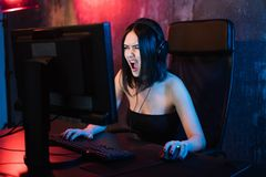 Screaming Emotional Young Angry Woman Playing On Personal Computer Holding Game Keyboard And Mouse Sitting On A Chair At Stock Images