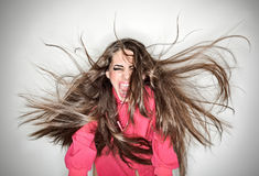 Screaming furious aggressive brunette woman. With flying long hairs, ring flash studio portrait on white stock photos