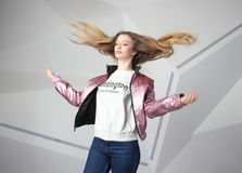 Screaming furious aggressive brunette woman with flying long hairs, flash studio portrait on modern wall. Screaming furious aggressive brunette woman with flying royalty free stock photos
