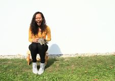 Screaming girl with cat. Portrait of pretty Papuan girl with curly hair dressed in yellow t-shirt, black pants and white shoes - screaming young Indonesian woman Stock Photography