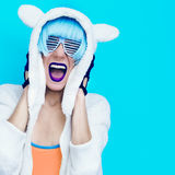 Screaming girl in hoodie Teddy Bear on a blue background. Royalty Free Stock Photo
