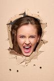 Screaming girl peeping through hole in paper Stock Images