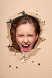 Screaming girl peeping through hole in paper Royalty Free Stock Photos