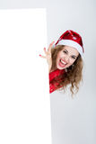 Screaming girl in red dress in a Christmas hat holding banners. Royalty Free Stock Images