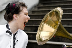 Screaming into gramophone. Young attractive woman dressed in forties style screaming into gramophone Stock Image