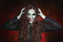 Screaming halloween beautiful vampire with long hair. In hell Stock Photo