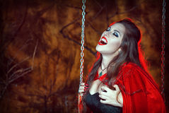 Screaming Halloween Woman In Red Cloak On The Swing Stock Images