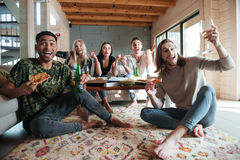 Screaming Happy Five friends sitting in house and eating pizza Stock Photos