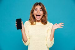 Screaming happy woman in sweater showing blank smartphone screen. And looking at the camera over blue background Stock Photography