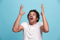 The young emotional angry man screaming on blue studio background Stock Photos