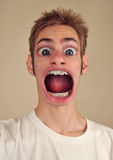Screaming with Huge Mouth. A young man screaming with huge eyes and mouth Stock Photography