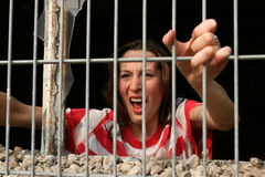 Screaming in jail. Woman behind bars in old jail, screaming Royalty Free Stock Photography