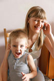 Screaming kid and mother with phone Royalty Free Stock Image