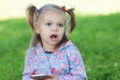Screaming little girl. Holding a mobile phone Stock Photography