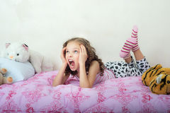 Screaming little girl lying on her bed royalty free stock photo