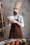 Screaming man baker standing with paper bag on head Royalty Free Stock Photography