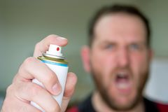Screaming Man Blurred Out Of Focus In The Background Hand In The Foreground With Insect Spray Stock Photos
