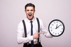Screaming man in business clothes holding and pointing at clock over white background stock image