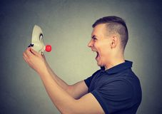 Screaming man with clown mask stock images