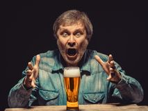 The screaming man in denim shirt with glass of Royalty Free Stock Photography