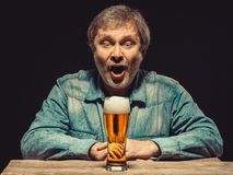 The screaming man in denim shirt with glass of Stock Image
