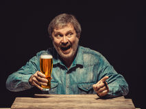 The screaming man in denim shirt with glass of. The front view of handsome screaming man as fan in denim shirt with glass of beer, sitting at the wooden table Stock Photography