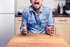 Screaming man gesturing with hands in his kitchen Royalty Free Stock Photos