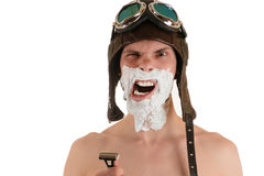 Screaming man with narrowed eyes with shaving foam on his face in flight helmet and flying goggles with razor Royalty Free Stock Photography