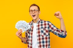 Screaming man in a plaid shirt holds money in his hands and looks into the camera on a yellow background royalty free stock photos