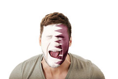 Screaming man with Qatar flag on face. Stock Photos