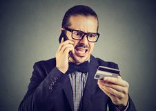 Screaming man solving problems with credit card stock images