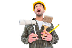 Screaming manual worker holding various tools Stock Photo