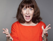 Screaming mature woman stimulating someone for success. Portrait of energetic beautiful 50's woman with both fists held strong for success and stimulation Royalty Free Stock Photo