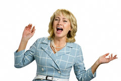 Screaming mature woman on white background. Blond adult woman with raised hands and open mouth screaming on white background close up Royalty Free Stock Photo