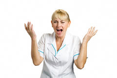 Screaming medical worker on white. Frustrated and shocked mature nurse with raised hands and open mouth standing on white background stock image