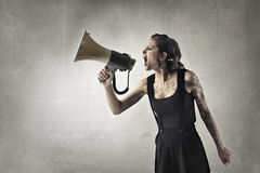 Screaming with megaphone. Woman is screaming with megaphone Stock Images
