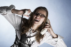 Screaming phone operator. Furious telephonist in call center wrapped with phone cables being overstrained with work, isolated on blue background Stock Images