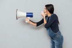 Screaming pregnant lady holding loudspeaker. stock image