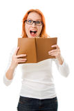Screaming red-haired girl in glasses with book. Stock Photography