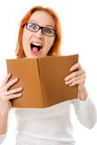 Screaming red-haired girl in glasses with book. Royalty Free Stock Images