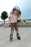 Screaming roller- first try. Little girl learning skating screaming of fear Royalty Free Stock Photos