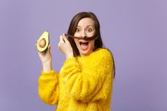 Screaming scared young woman keeping hair like mustache holding half of fresh ripe avocado isolated on violet pastel. Wall background. People vivid lifestyle stock image