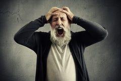Screaming senior man with closed eyes Stock Image