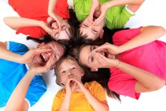 Screaming siblings in circle. Screaming children laying in a circle wearing colorful tee shirts Stock Photography