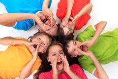 Screaming siblings in circle. Screaming children siblings laying in a circle wearing colorful tee shirts Royalty Free Stock Photo