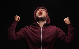 Screaming, sick male on a black background. Stressed student in a hoodie. Man suffering in pain. Anger issues concept. Royalty Free Stock Photos